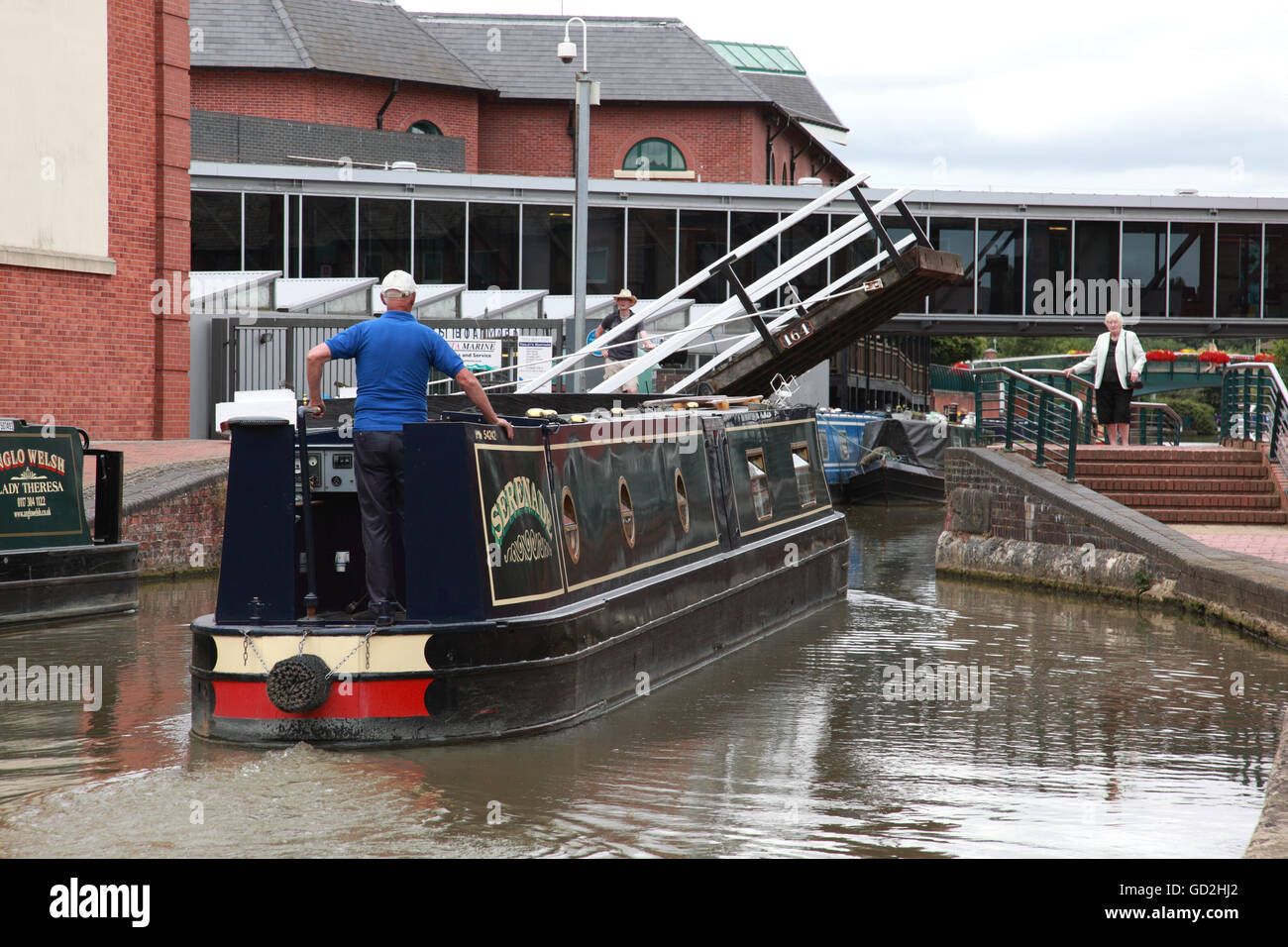 A narrowboat going under the lift bridge on the Oxford Canal in Banbury with the Castle Quay shopping centre on - Stock Image