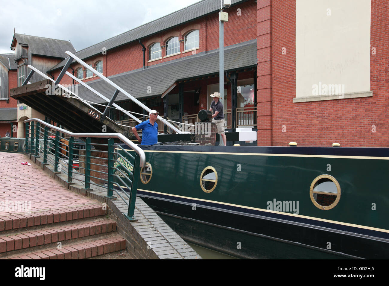 A narrowboat going under the lift bridge on the Oxford Canal in Banbury with the Castle Quay shopping centre in - Stock Image