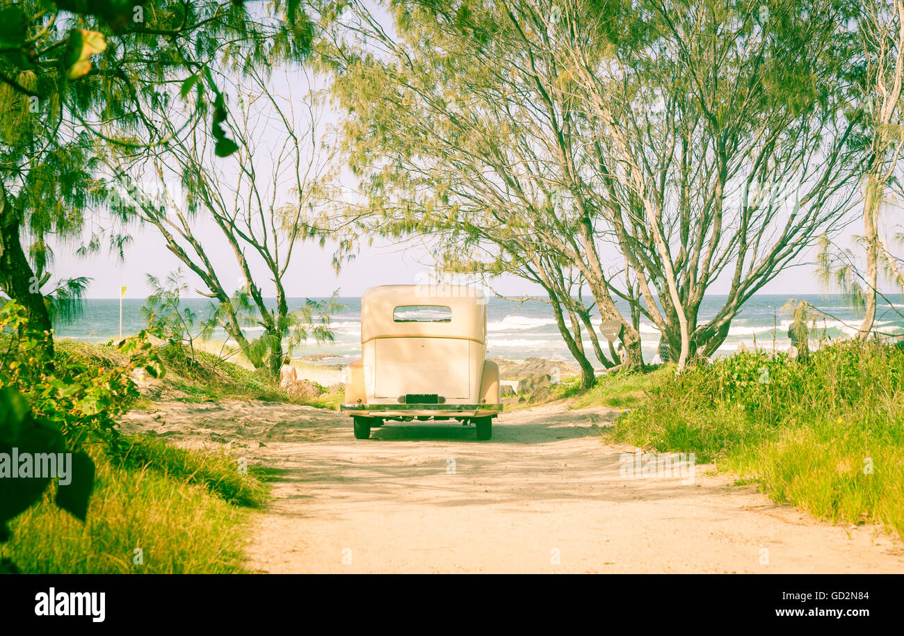 Vintage car parked at end of dirt track leading to beach under trees in retro filter tones. - Stock Image