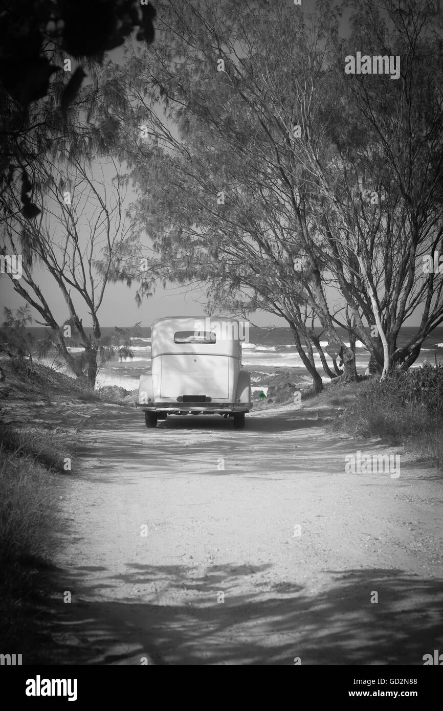 Vintage black and white grainy image old fashioned car parked at end of dirt track leading to beach under shady - Stock Image