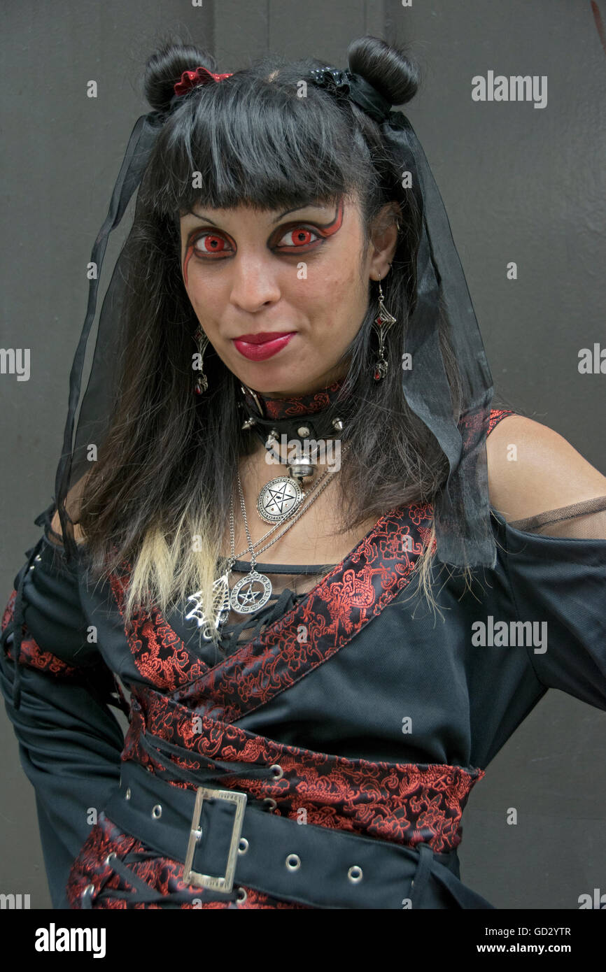 A girl wearing red costume contacts at WitchsFest USA  in Greenwich Village, New York City - Stock Image