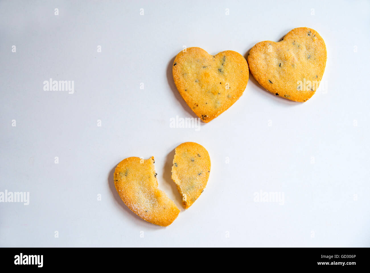 Three heart-shaped biscuits, one of them broken in two pieces. - Stock Image