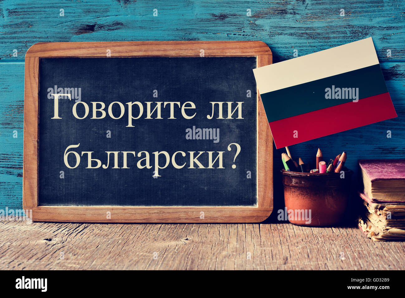a chalkboard with the question do you speak Russian? written in Russian, a pot with pencils, some books and the - Stock Image