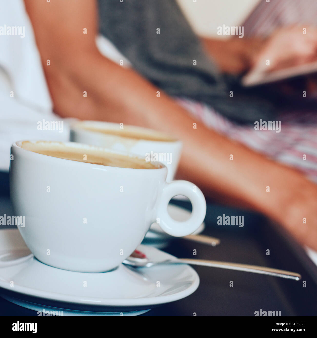 closeup of two cups of coffee in the foreground and a young caucasian man in pajamas in bed using a tablet computer - Stock Image