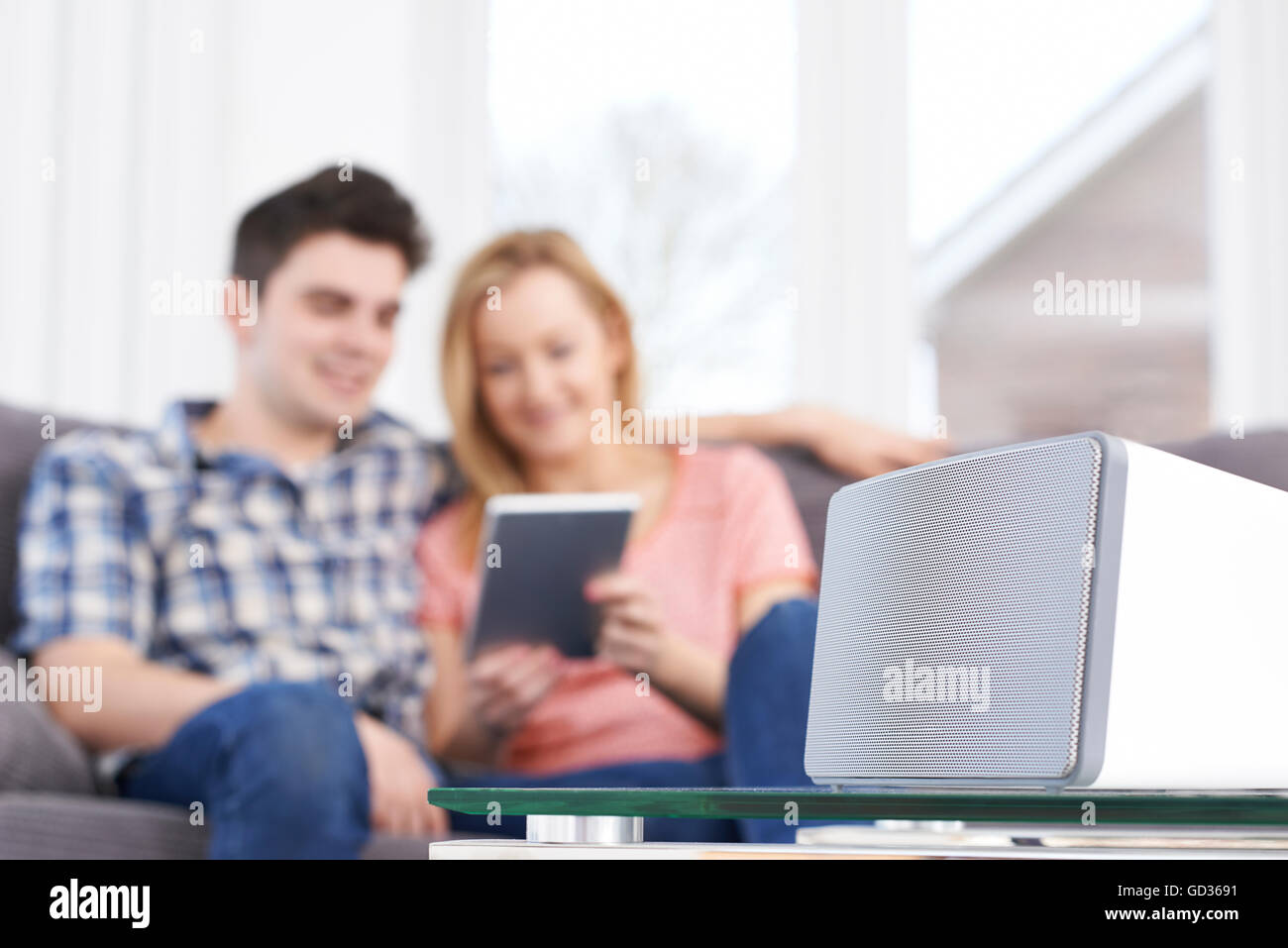 Couple Streaming Music From Digital Tablet To Wireless Speaker - Stock Image