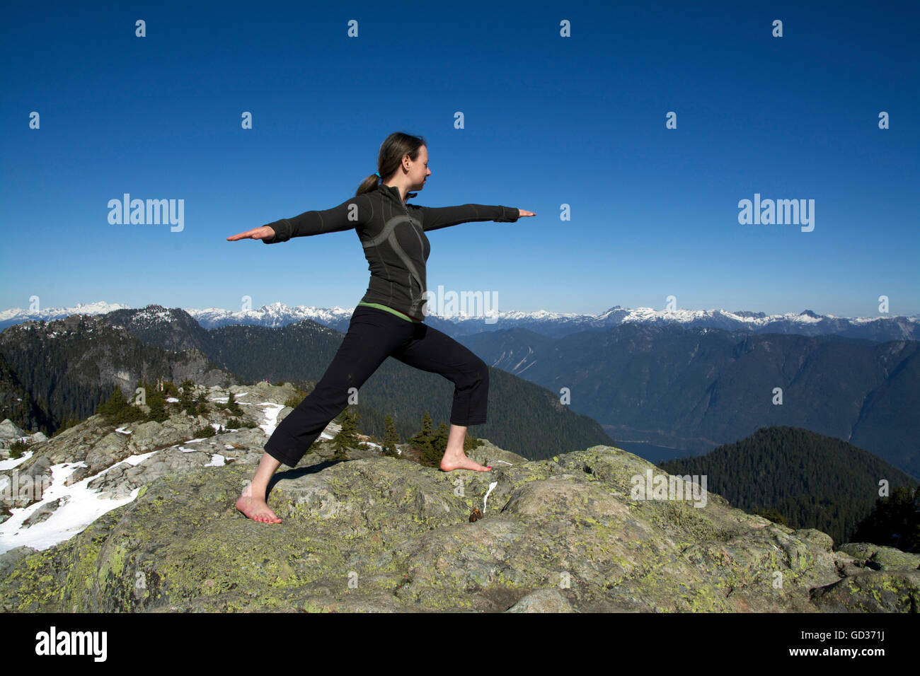 Middle Aged Caucasian Woman Holding Hatha Yoga Warrior Pose on Winter Snowcap Sunshine Mountain Peaks with Blue - Stock Image