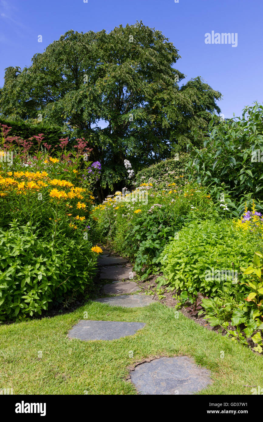 Stepping stones lead through a lawn and herbaceous border at the Garden House, Devon, UK. - Stock Image