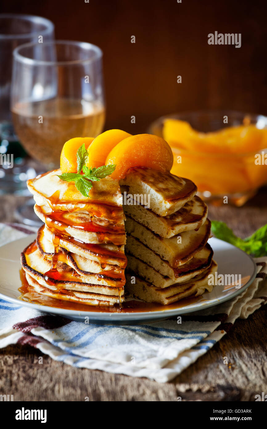 Stack of homemade pancakes with poached peaches - Stock Image