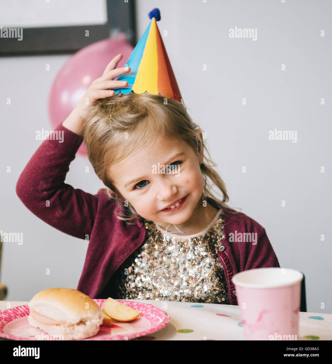 A young girl in a party hat at a birthday party. - Stock Image