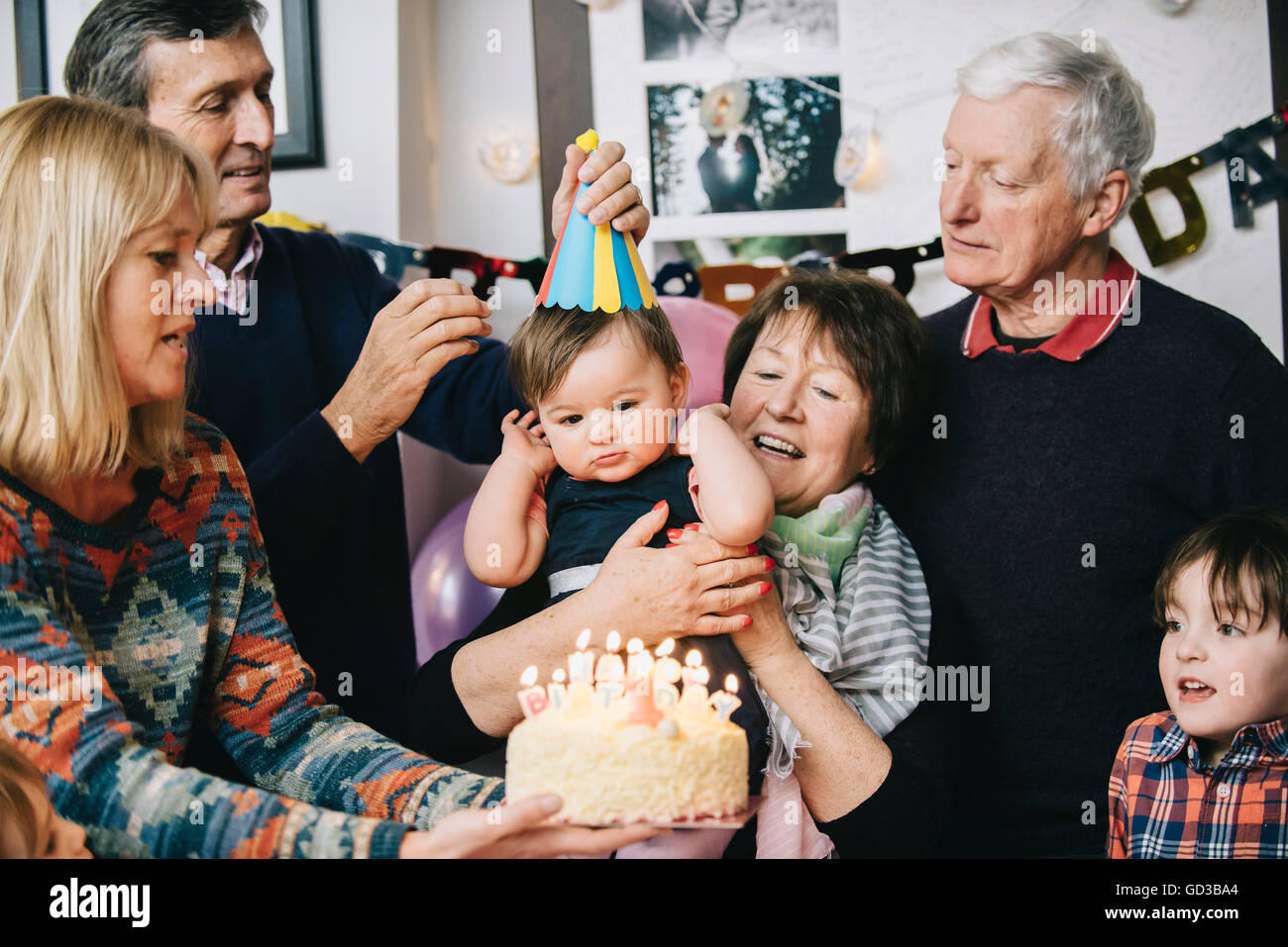 A family gathered to celebrate a one year old girl's birthday party. A cake with lots of candles. Stock Photo