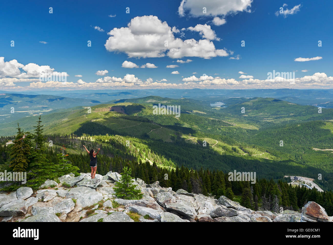 Woman standing on the edge of rocks, arms in the air - Mount Spokane in washington, USA. Stock Photo
