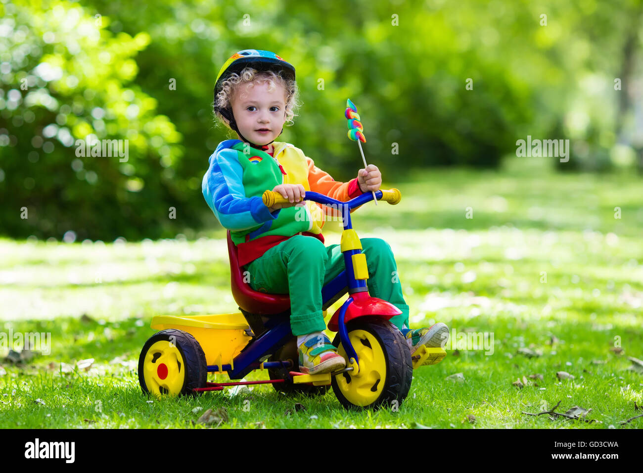 8973c4351bb Cute girl wearing safety helmet riding her tricycle in sunny summer park.  Kids ride bicycle. First bike for little child.