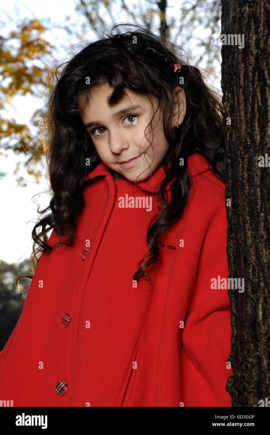 Five year old girl in red coat standing near a tree in a park Stock Photo