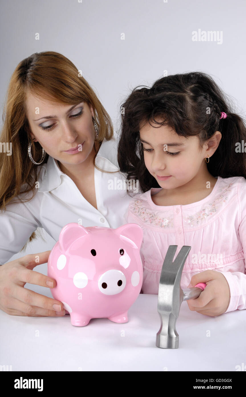 Mother with her young daughter intending to break a piggy bank - Stock Image
