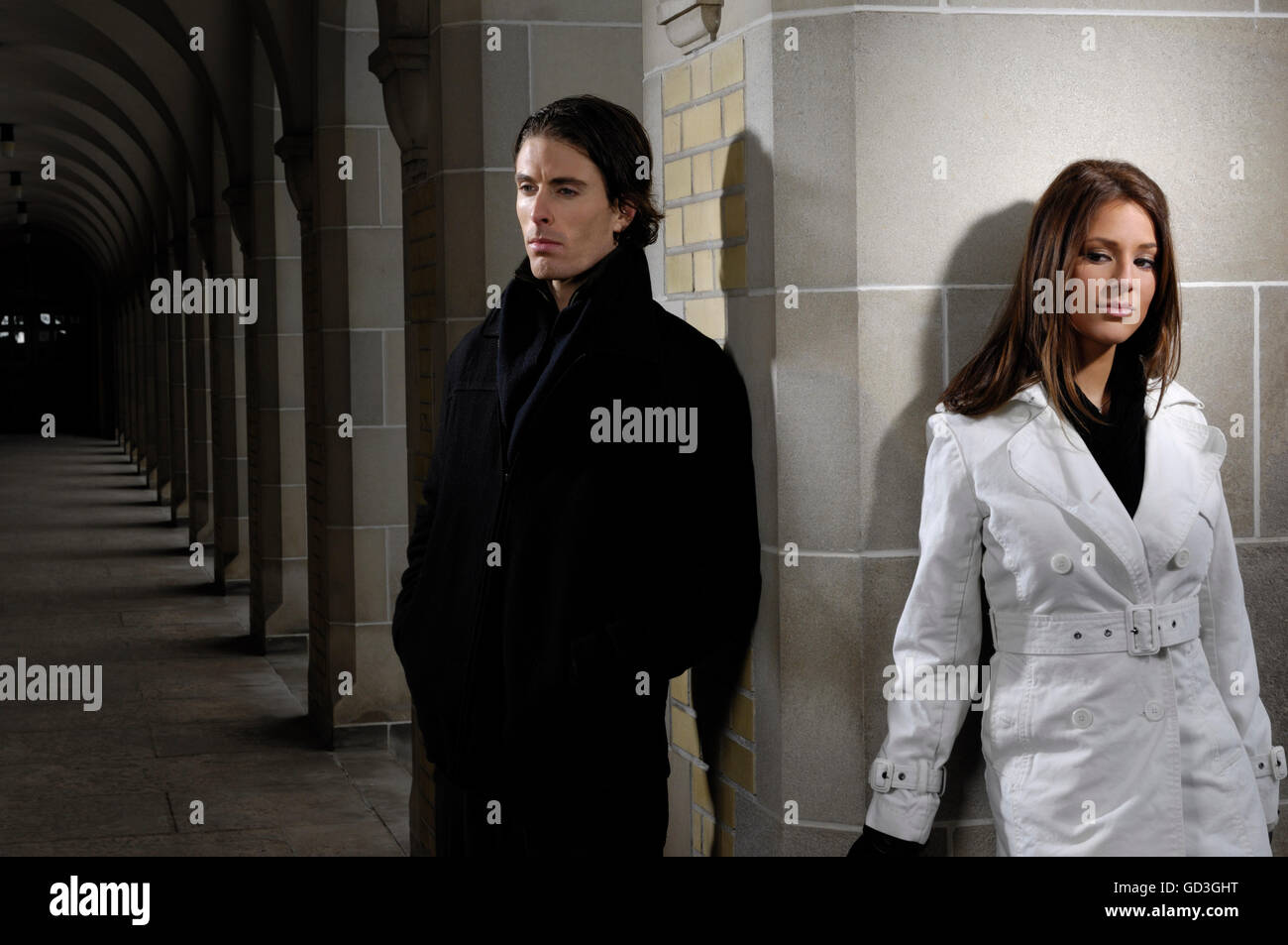 Young man and a woman standing apart not looking at each other, quarrel, relationship problems - Stock Image