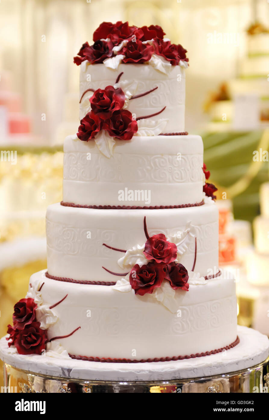 Tiered wedding cake decorated with red roses - Stock Image