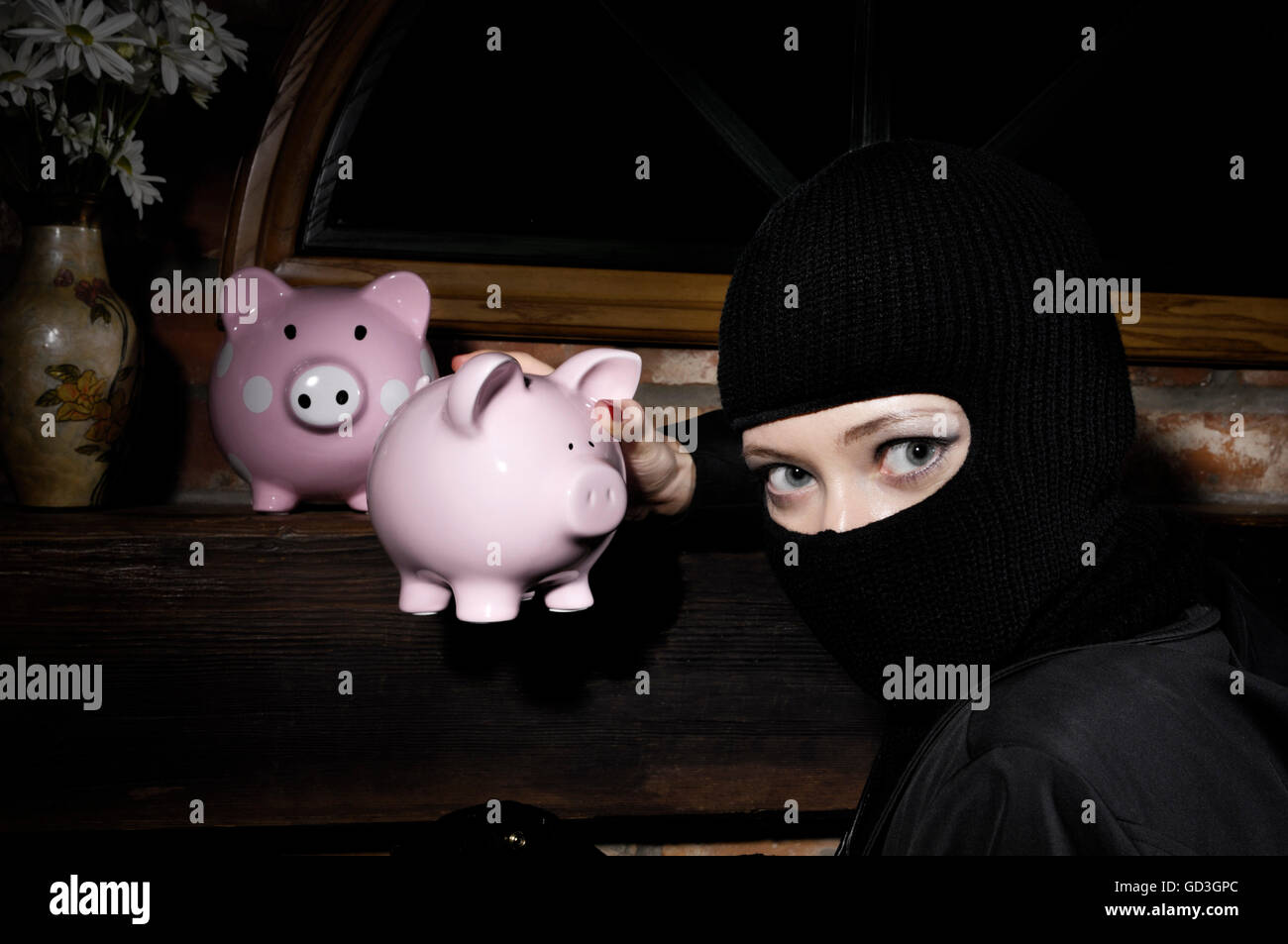 Caught by surprise burglar stealing piggy banks from a house at night - Stock Image