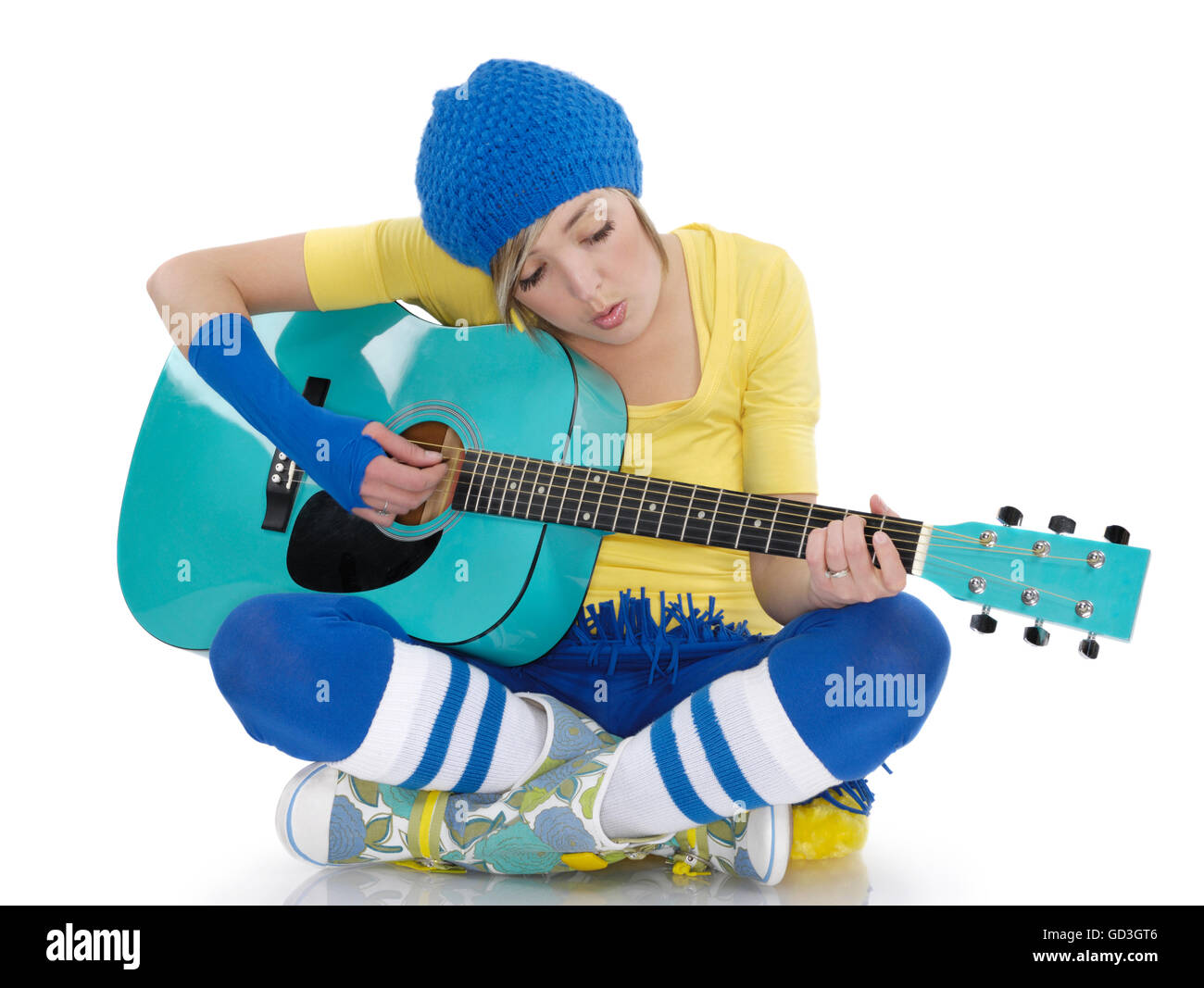 Young woman sitting on the floor and playing the guitar - Stock Image