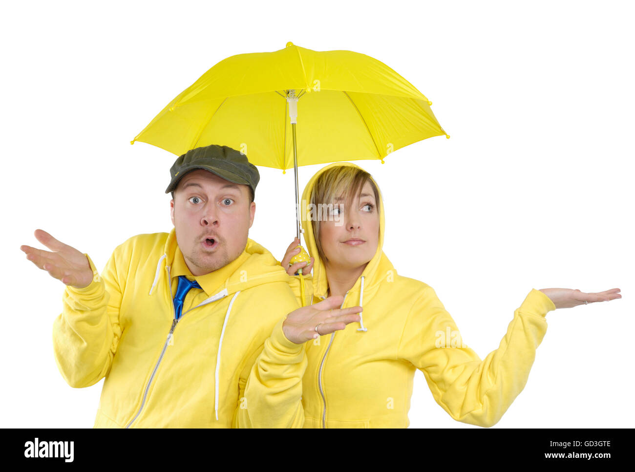 Young couple under a small yellow umbrella - Stock Image