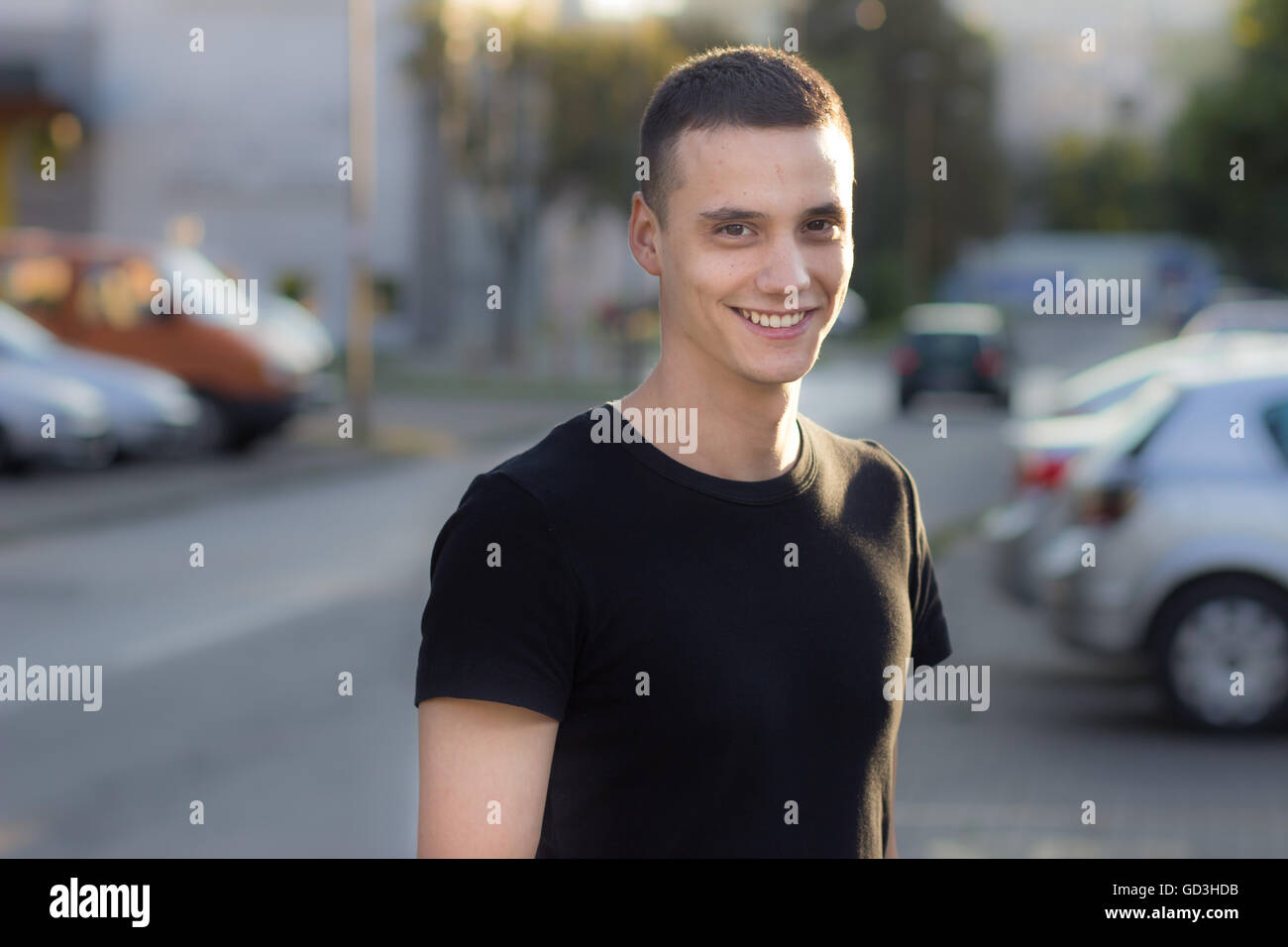 Young man in early 20s smiling portrait outdoors. Shallow depth of field, blur out od focus background. - Stock Image