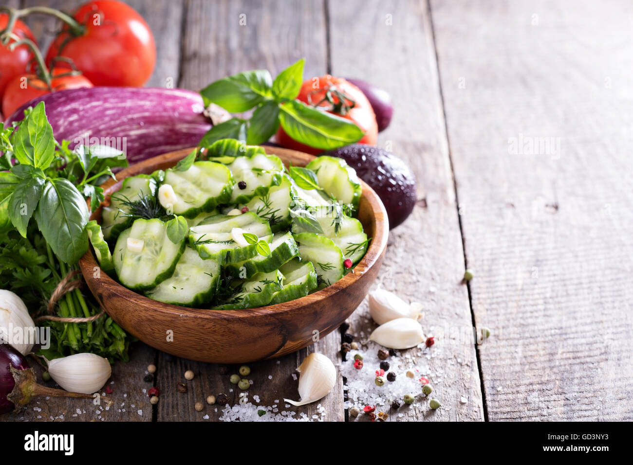 Pickled cucumber in a rustic wooden bowl - Stock Image