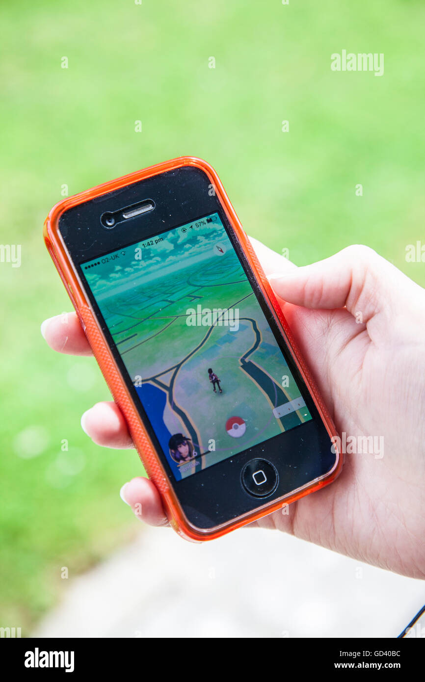 A young person uses an iPhone to play Pokémon GO, the latest augmented reality mobile app game to hit the worldwide - Stock Image