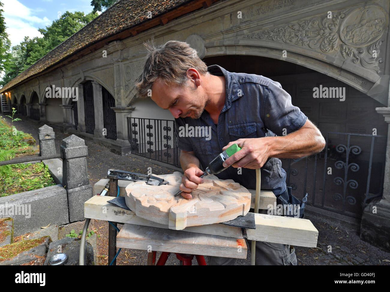 Sculptor Martin Roedel working on a sandstone relief in front of the arcade arches at Stadtgottesacker in Halle/Saale, Stock Photo