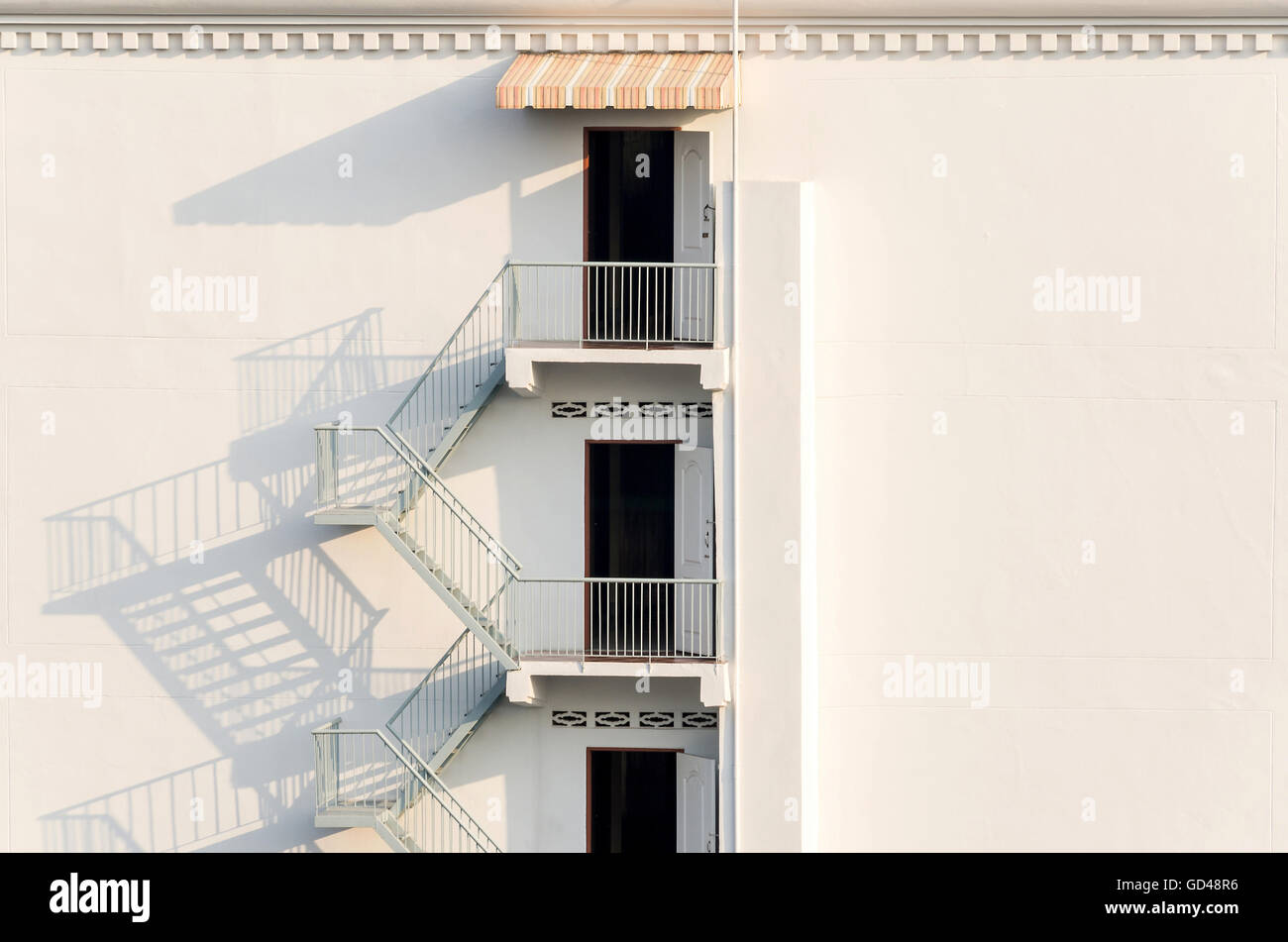 fire escape with afternoon shadows on exterior white wall. - Stock Image