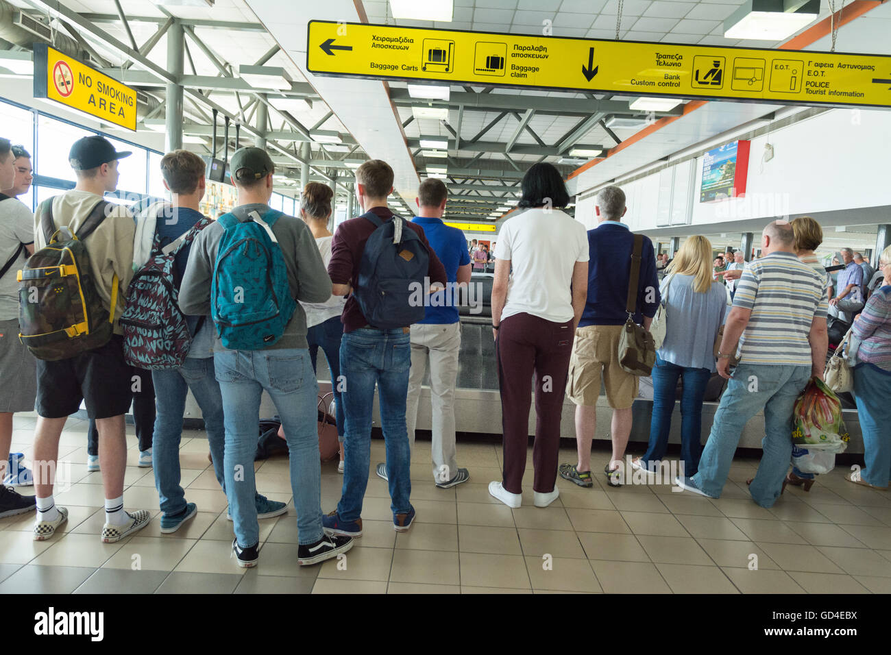 Baggage reclaim - people waiting at Corfu airport to claim baggage from the carousel - Stock Image