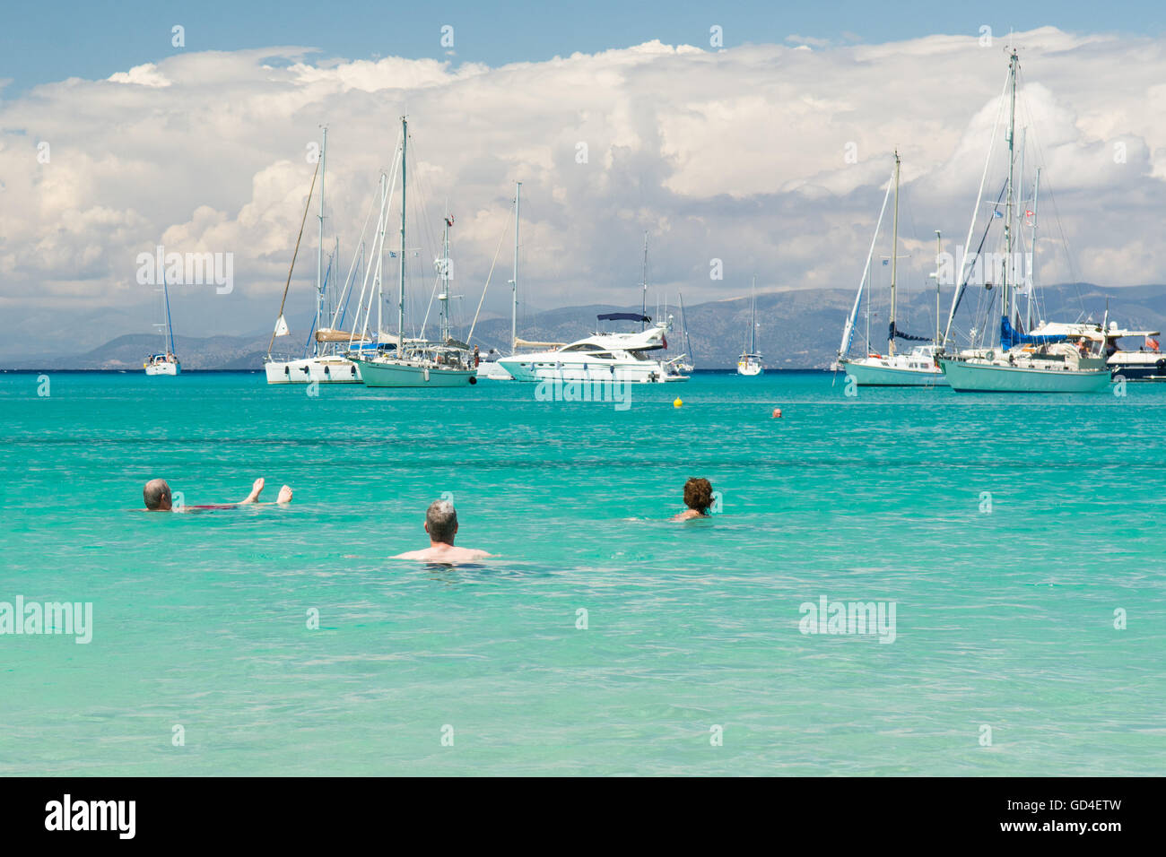 holidaymakers relaxing in the clear turquoise sea at Lakka, Paxos - looking out towards luxury boats moored offshore - Stock Image
