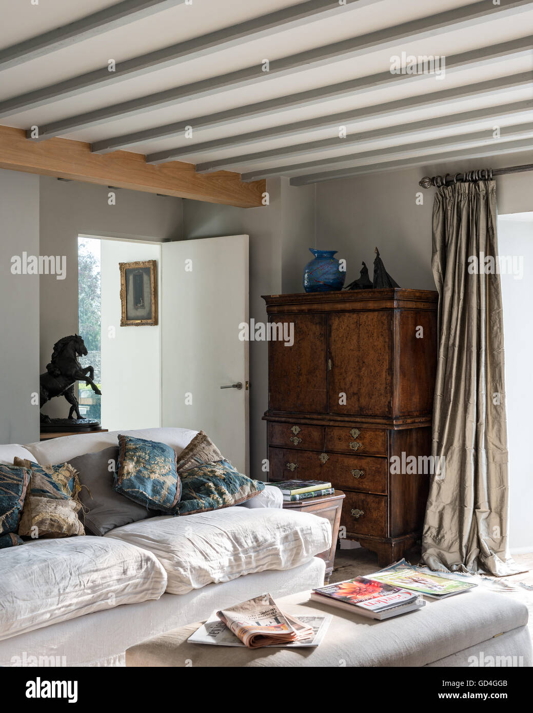 Antique wooden cabinet and equestrian statue with linen sofa in cosy living room - Stock Image