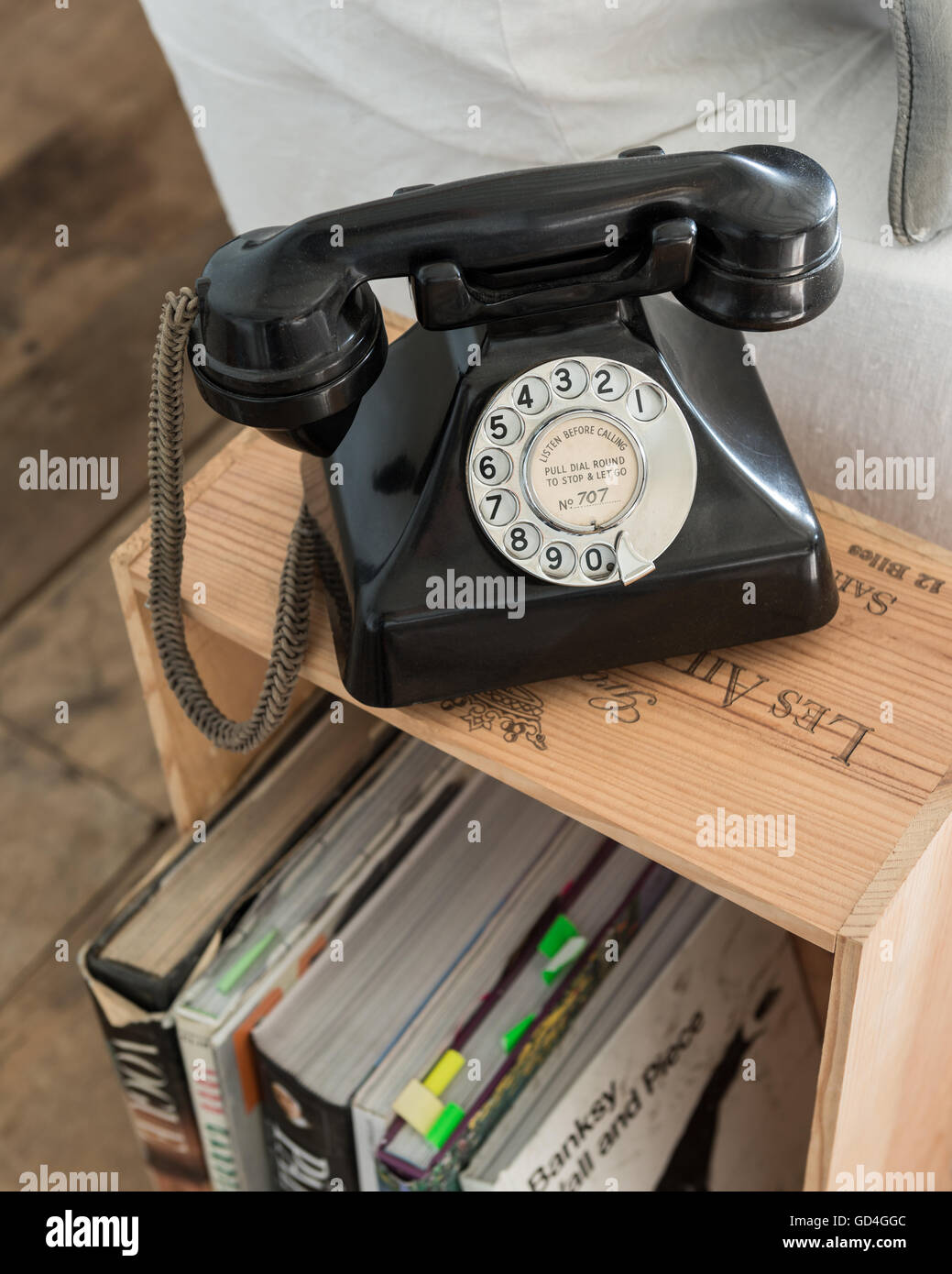 Bakelite telephone on wine crate used as side table - Stock Image
