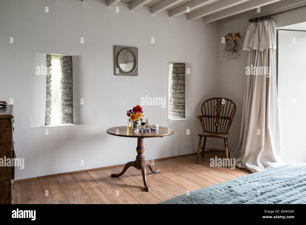Wooden chair with pedestal base table in bedroom - Stock Image