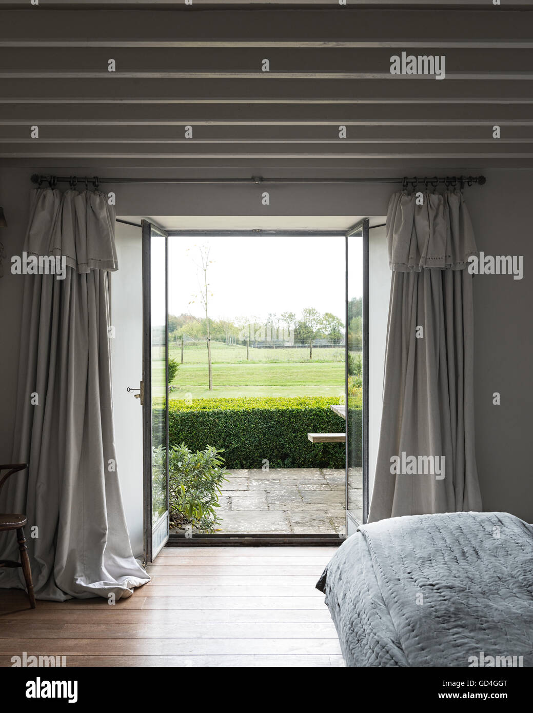 View Through Open Glass Door With French Linen Curtains Through To Stone  Terrace And Garden