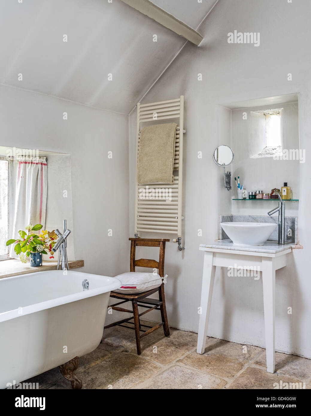 Heated radiator and wash basin with vintage wooden chair in bathroom - Stock Image