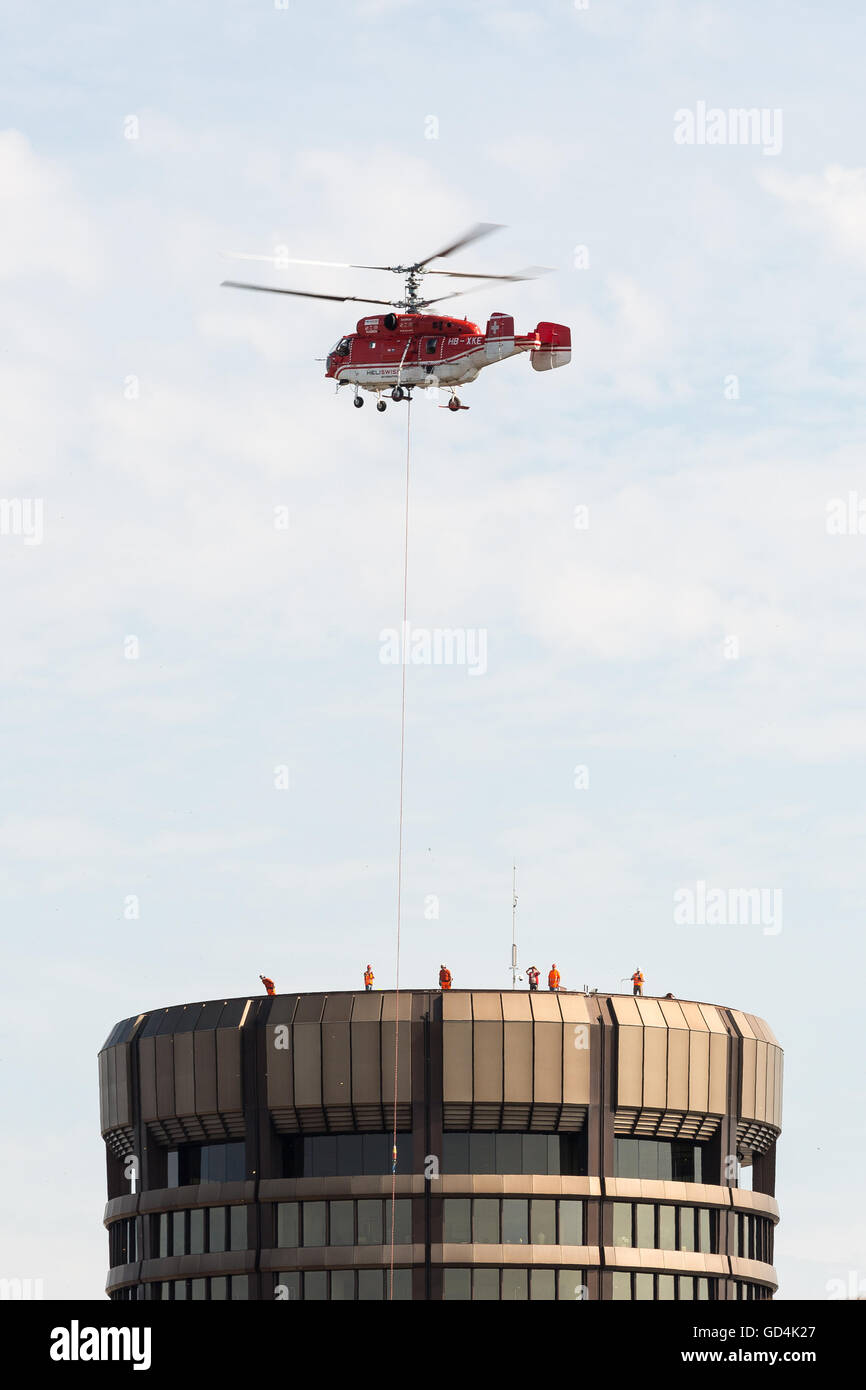 Heliswiss International AG performing equipment air lift for maintenance on the Bank for International Settlements - Stock Image