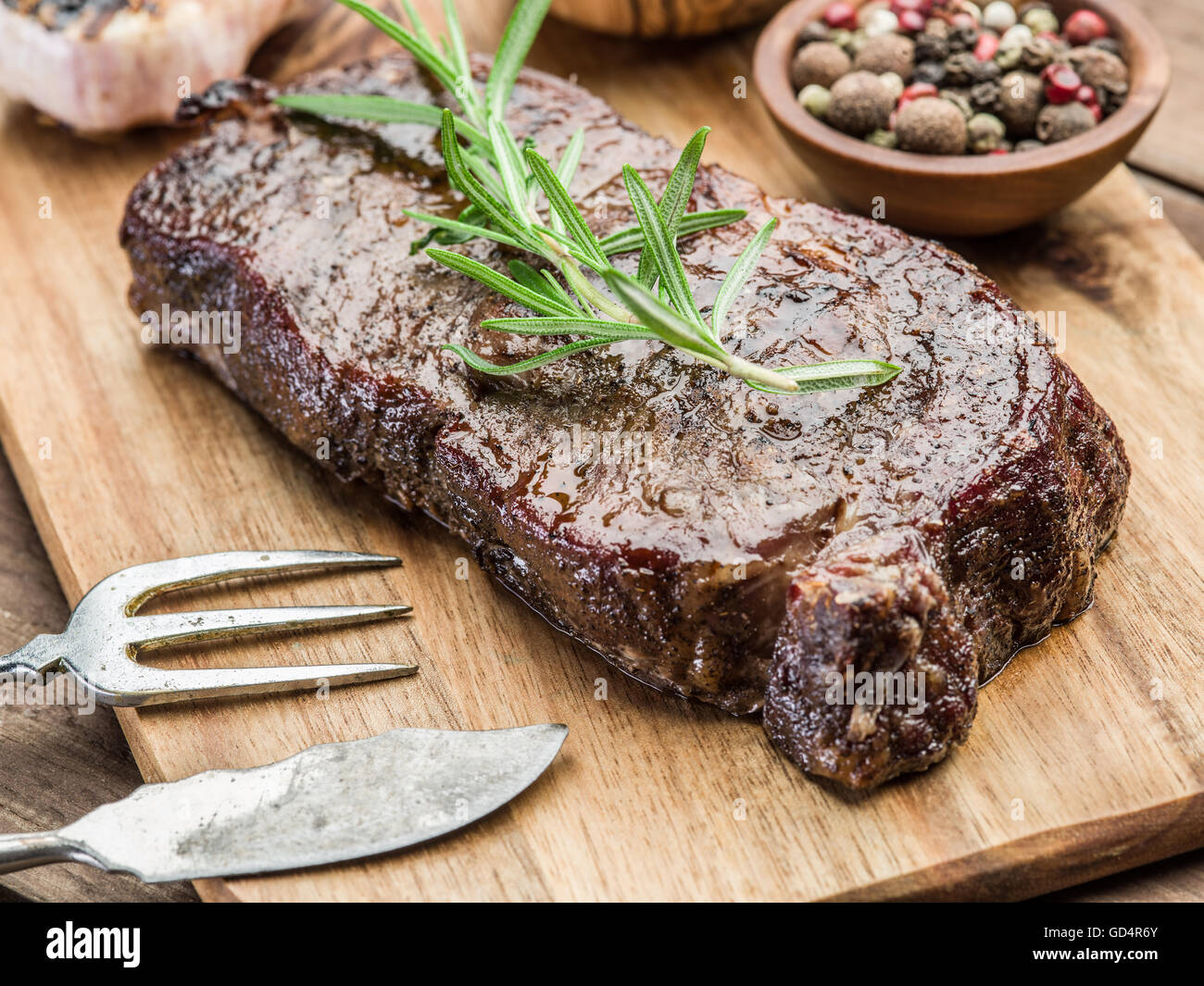 Steak Rib eye with spices on the wooden tray. - Stock Image