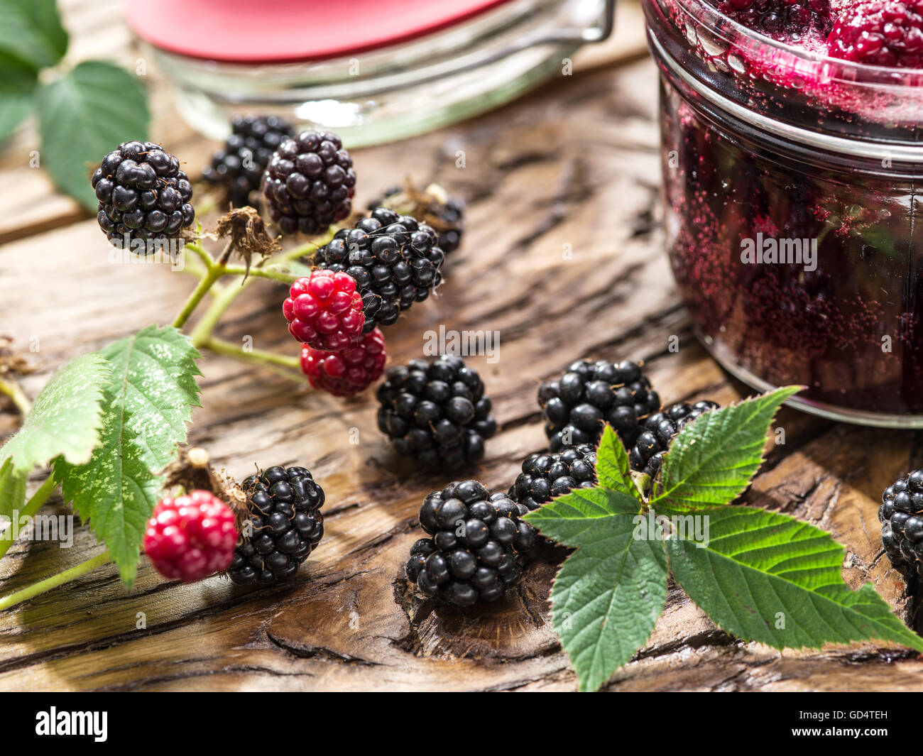 Blackberry confiture on old wooden table. Several fresh berries are near it. - Stock Image