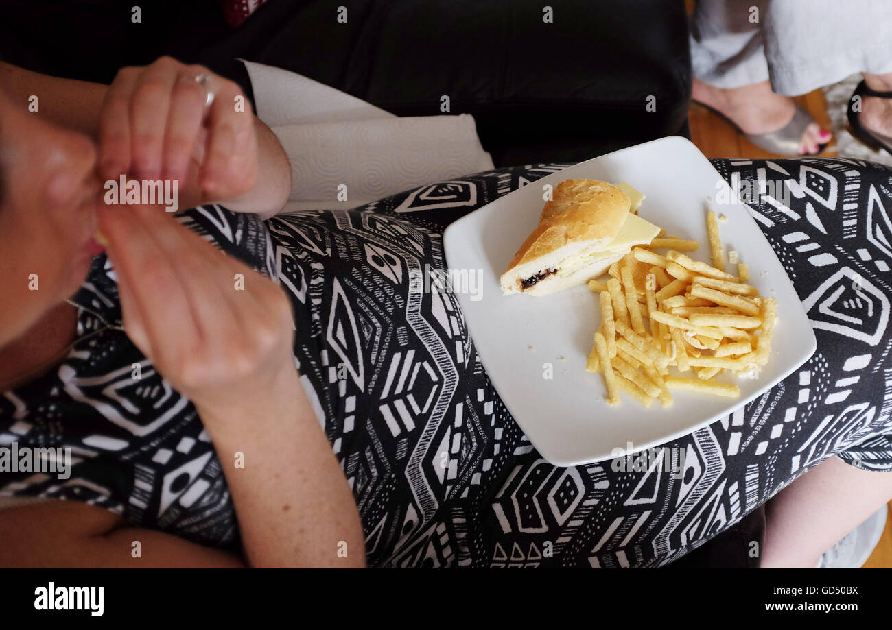 Young pregnant woman eating unhealthy diet of white bread cheese roll and potato chips fast food - Stock Image