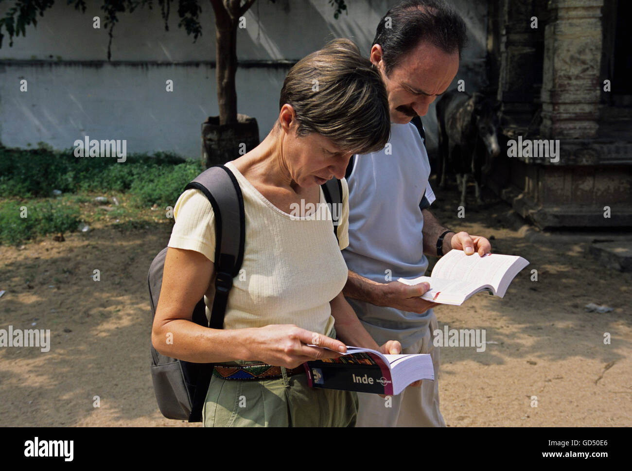 Foreigners Going Through Guide Book - Stock Image