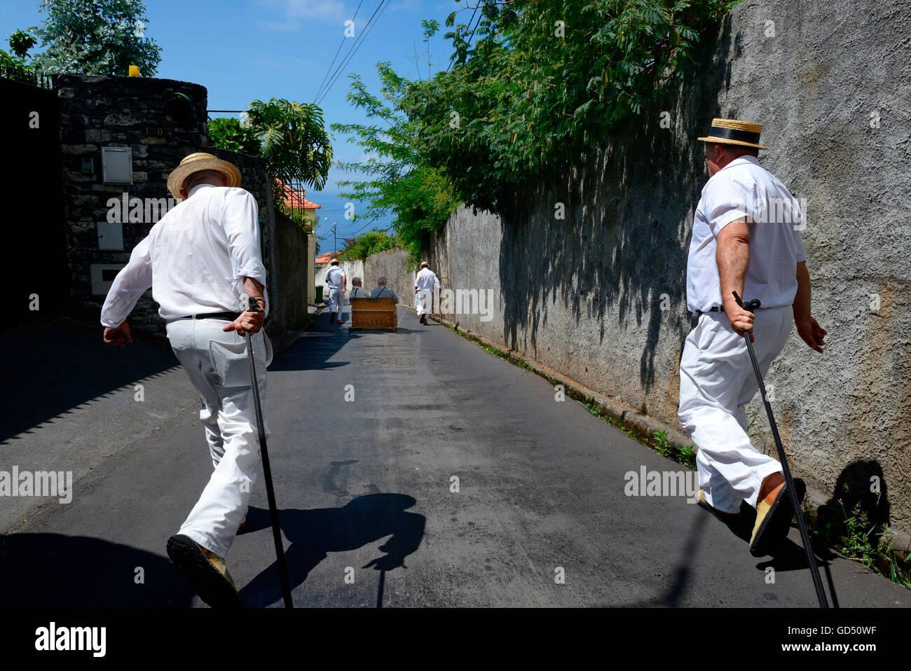 Fahrt mit dem Korbschlitten, Maenner ziehen und stossen Korbschlitten, Monte, Funchal, Madeira, Portugal, Europa - Stock Image