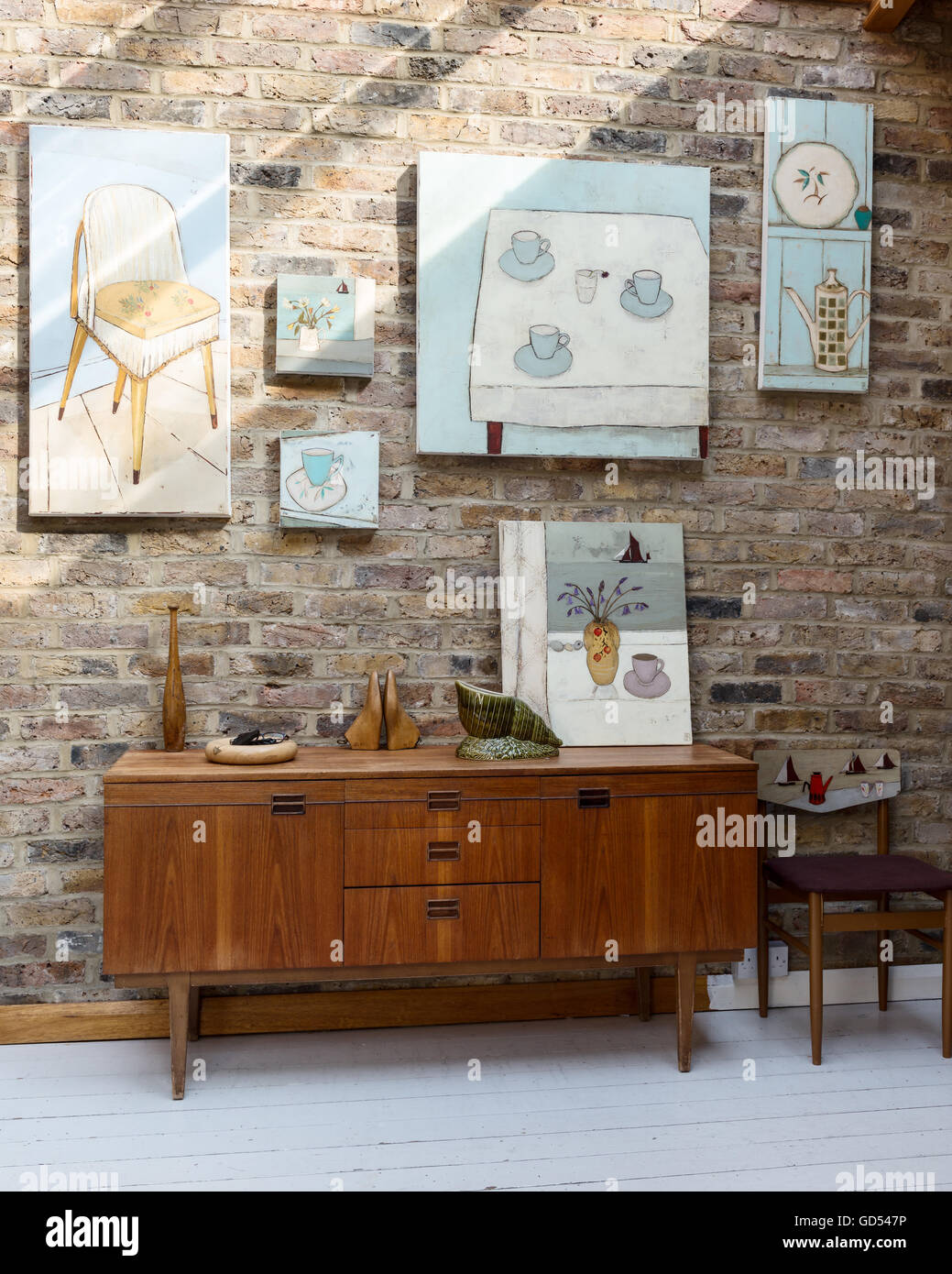 Retro sideboard in hallway with exposed brick walls and assorted artworks by Jo Oakely - Stock Image
