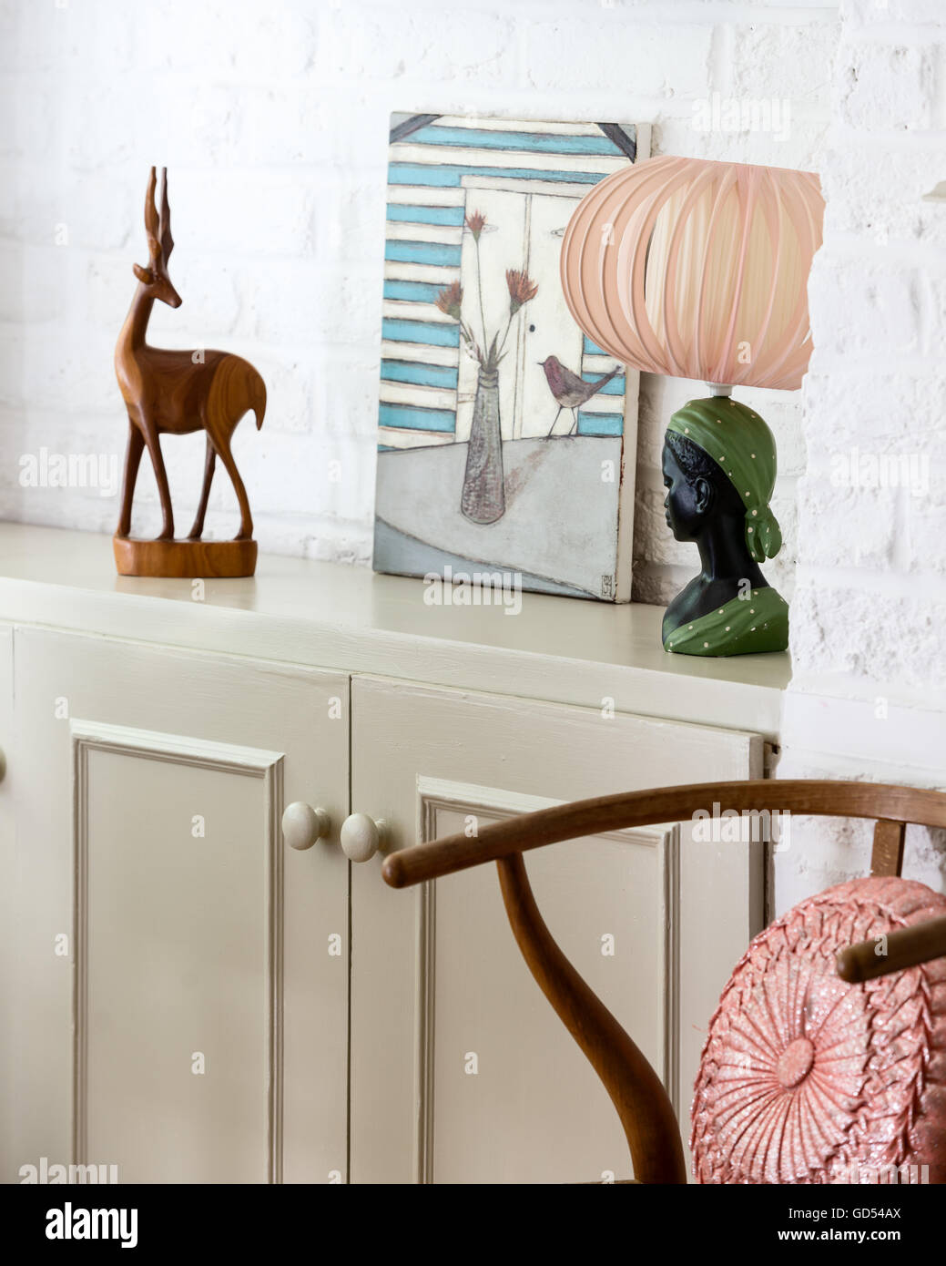 Antelope wood carving with kitsch lamp and small Jo Oakley painting - Stock Image