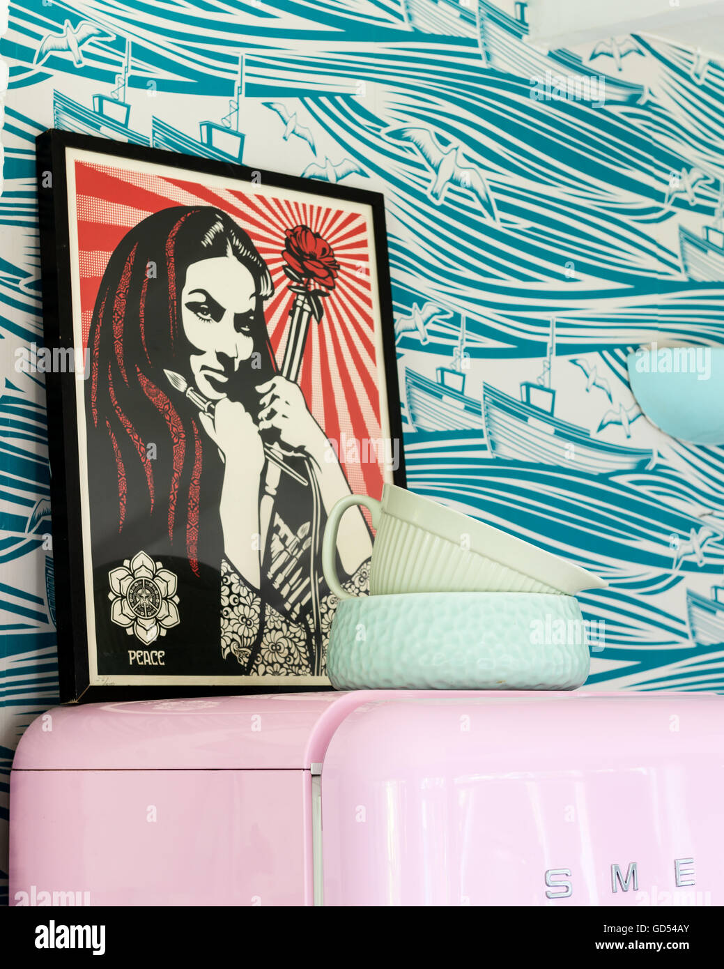 Shepard Fairey art on pink retro Smeg fridge. The wallpaper is Whitby by Mini Moderns - Stock Image