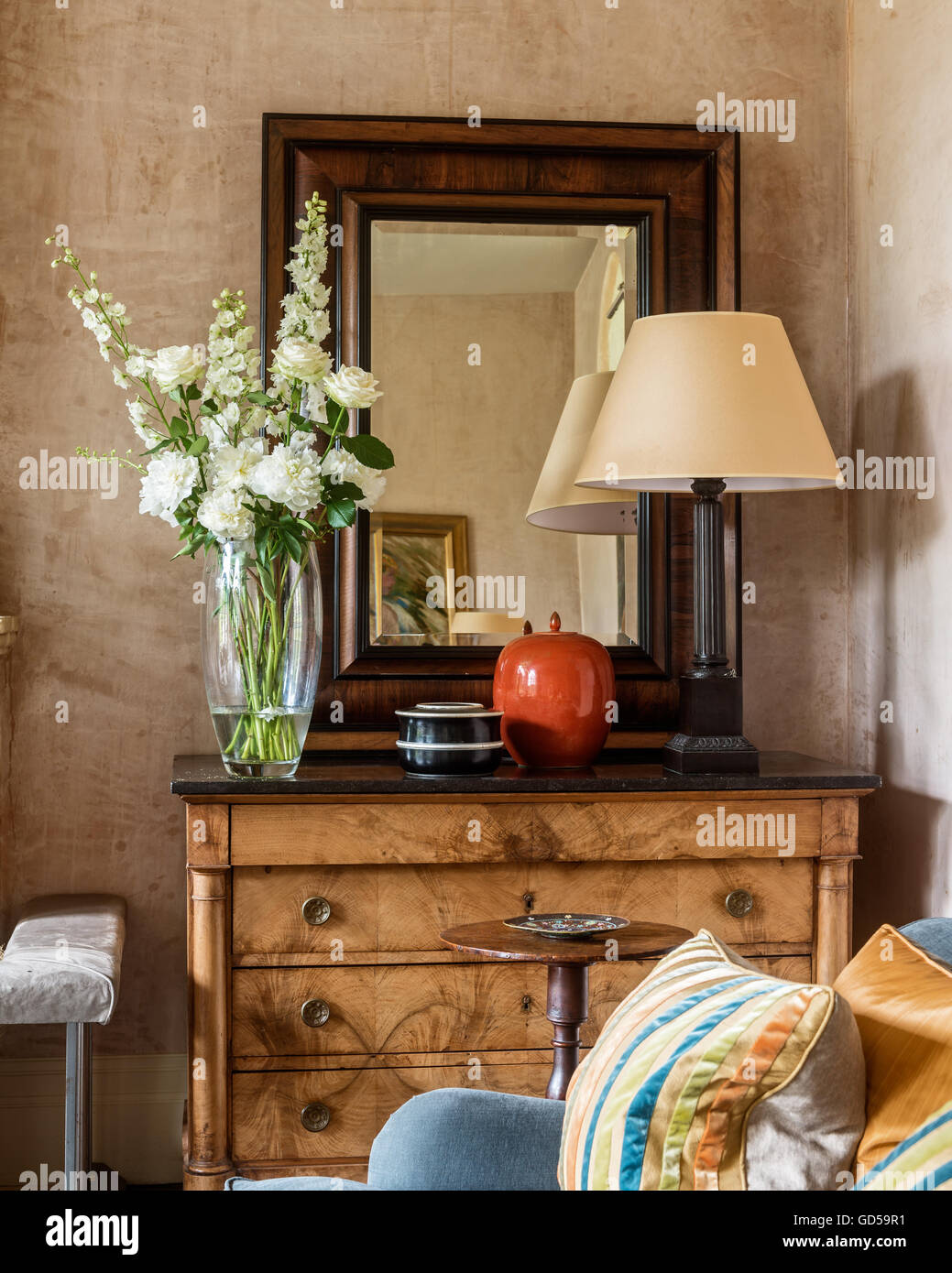 Antique wood framed mirror on chest of drawers with lamp and vase - Stock Image