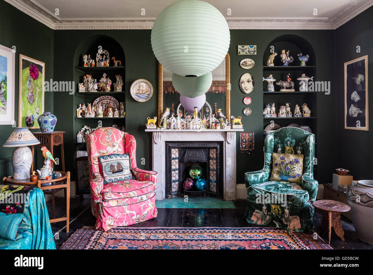 Large kilims and assorted artwork in eclectic drawing room painted in Sherwood Green by Farrow & Ball. Fornasettie - Stock Image
