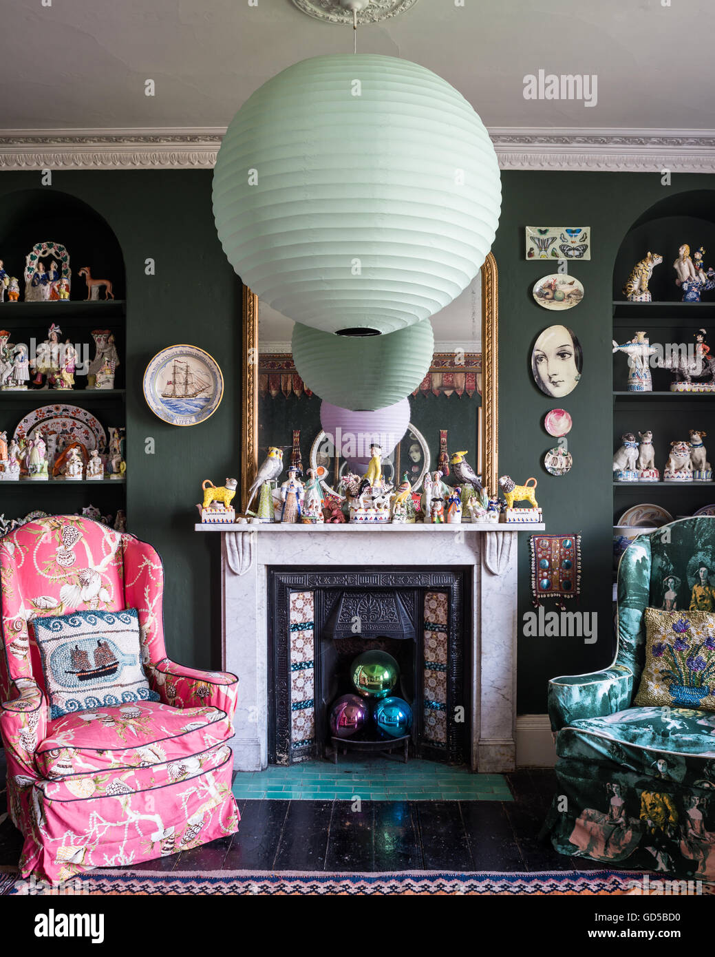 Eclectic drawing room painted in Sherwood Green by Farrow & Ball. Fornasettie plates, Stafforshire figures and - Stock Image