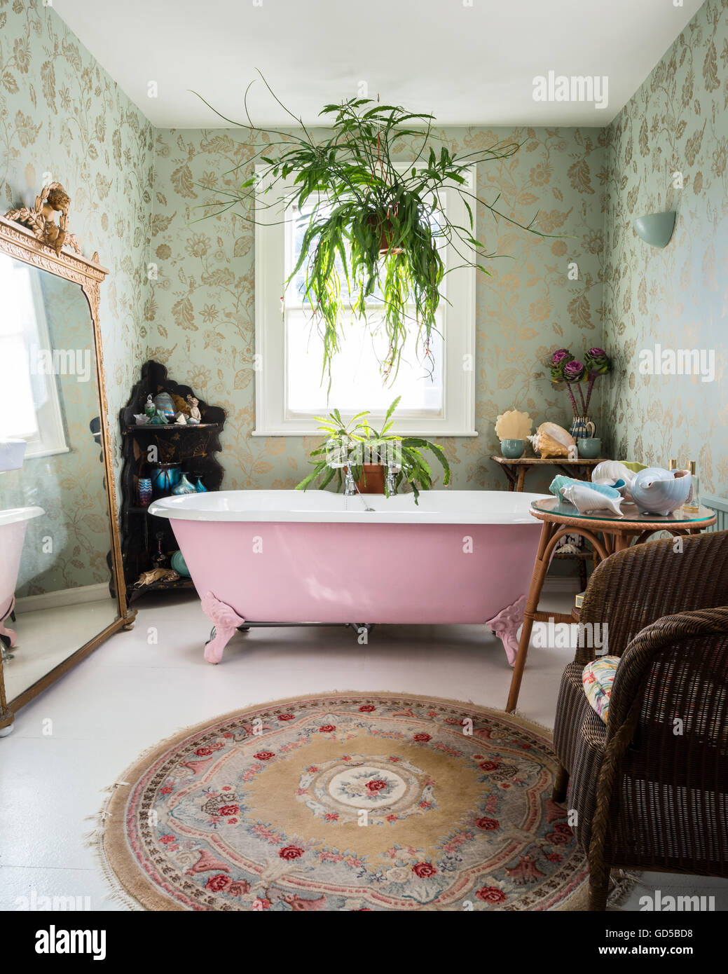 Pink double ended, roll top, freestanding bath in bathroom with Colefax & Fowler print wallpaper and large giltwood - Stock Image