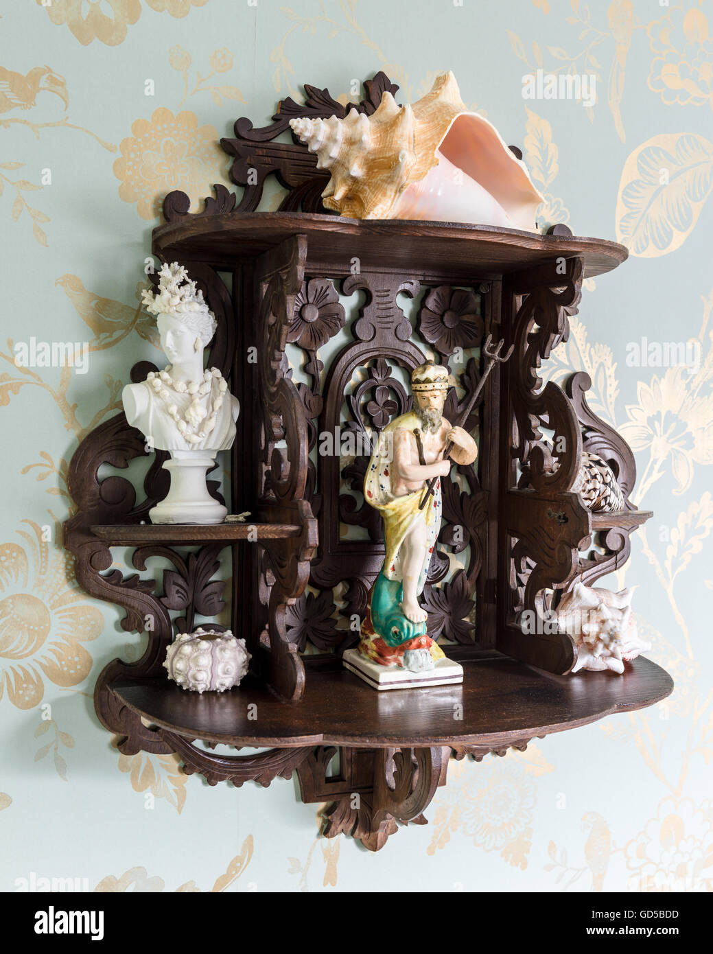 Staffordshire figures and shells on decorative hanging shelf with Colefax & Fowler wallpaper backdrop - Stock Image