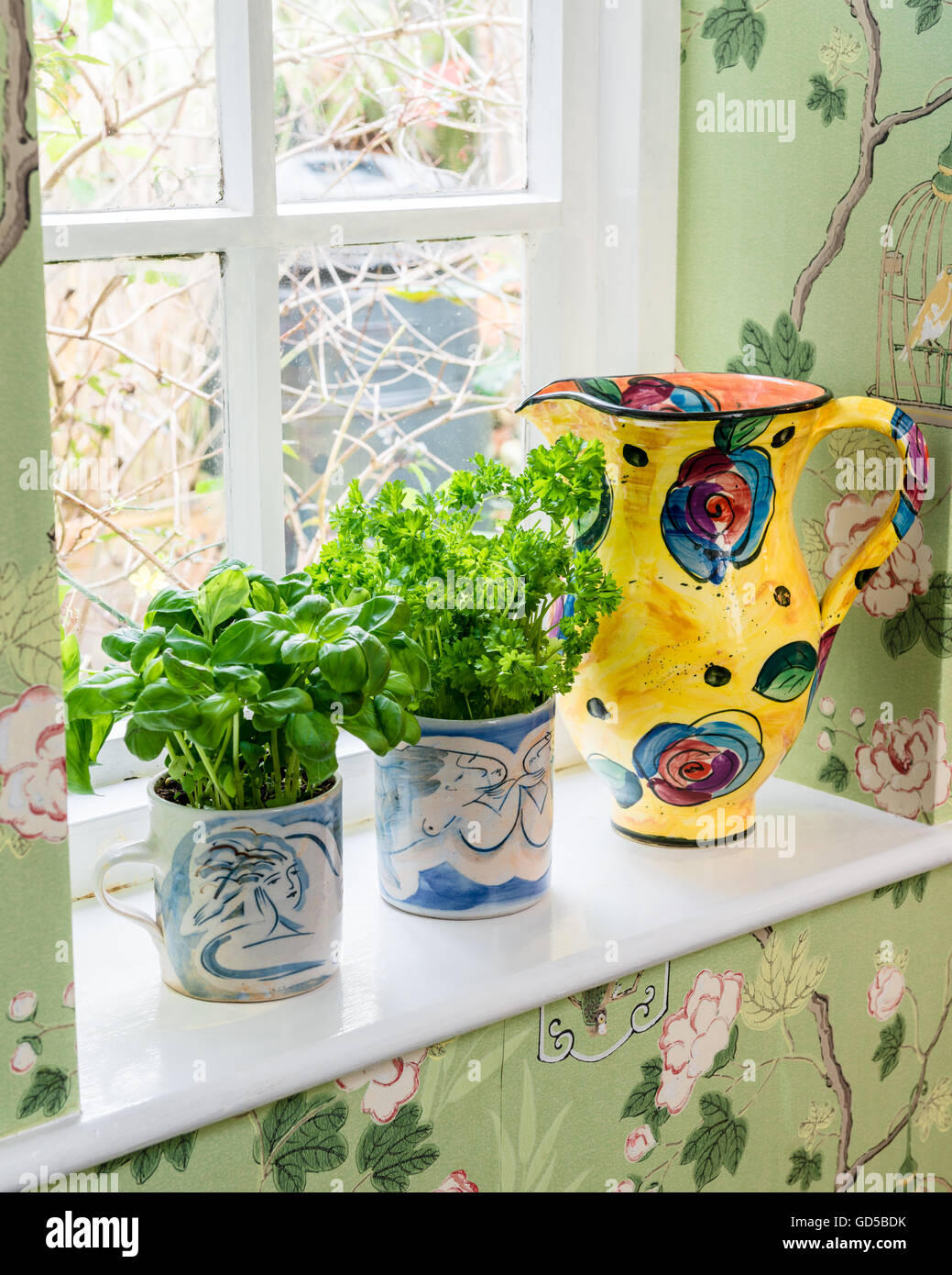 Vibrant coloured jug by Mary Rose Young on window sill with hand painted mugs by Julia Quigley holding basil and - Stock Image